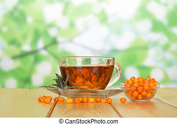 Bowl sea buckthorn berries and cup tea on abstract green - A...