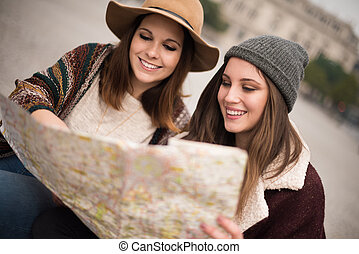 Friends consulting a city map - Female friends consulting a...