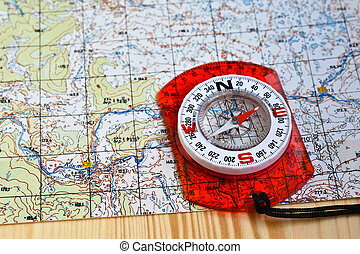 Orienteering using a map and compass Magnetic compass on a...