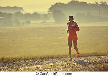 Early morning run - Fit young lady in red summer sportswear...