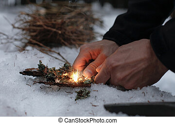 Man lighting a fire in a dark winter forest, preparing for...