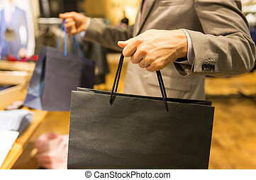 close up of man with shopping bags at store