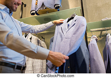close up of man choosing jacket at clothing store
