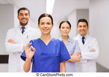 group of medics at hospital showing ok hand sign - clinic,...