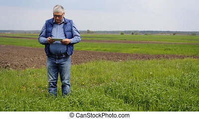 A man using his tablet on the field.