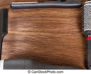 Combs, dryers and curling irons on background smooth brown...