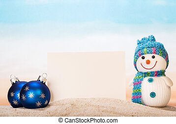 Blank white postcard, snowman , Christmas balls in sand...