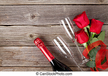 Red roses and champagne over wooden background. Top view...