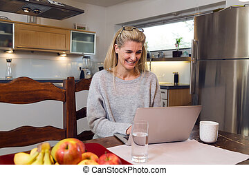 Middle-aged attractive woman using a laptop computer at home