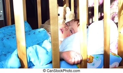 the baby sleeps in a cot - child sleeping sweetly in the...