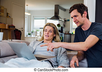 Couple at home on sofa looking at laptop - Joyful couple...
