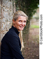 woman leaning against wall in park - attractive middle aged...