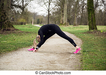 attarcive woman stretching in park
