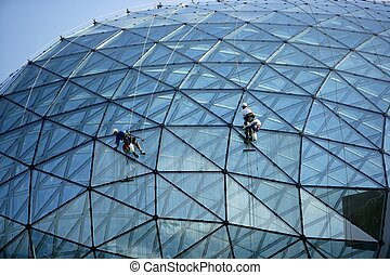 Climber cleaning mirror glass dome building  climbing ropes