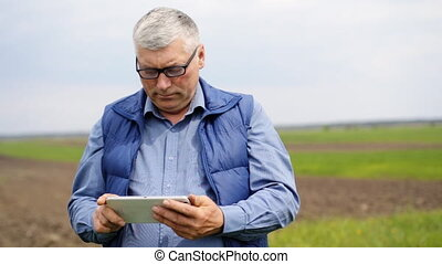 Serious farmer  using his tablet on the field.