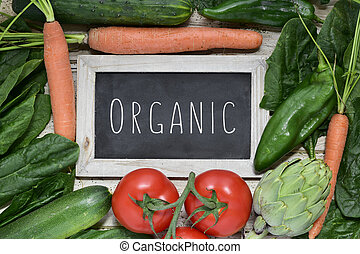 raw vegetables and text organic on a chalkboard - closeup of...