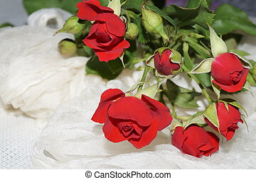 Bouquet of red roses on white silk