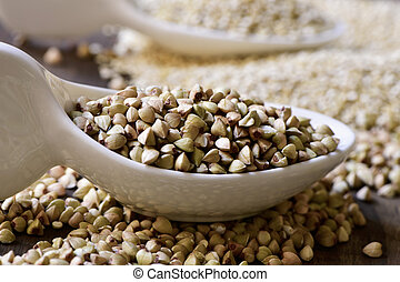 buckwheat and quinoa seeds - closeup of some ceramic spoons...