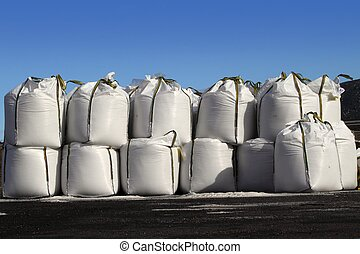 salt big bags sacks stacked rows for iced roads blue sky