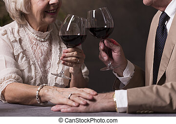 Proposing a toast - Cropped picture of an old couple...