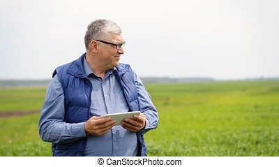 Healthy farmer staying on the field and using his tablet.