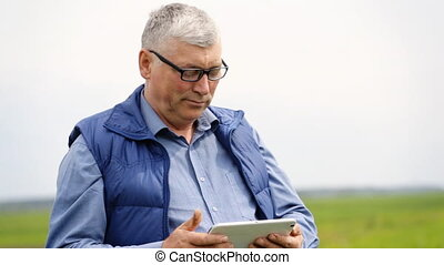 Serious senior look on a camera but doesn`t stop to search something on his tablet.