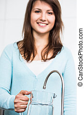 Tap water has got many benefits - Smiling young woman...