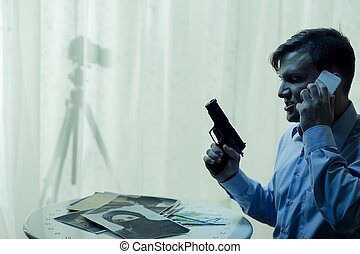 I'm ready to action - Man holding gun, talking on cellphone,...