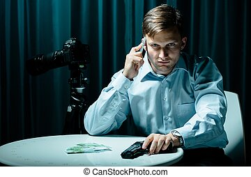 Pay or die! - Killer talking on cellphone, holding gun,...