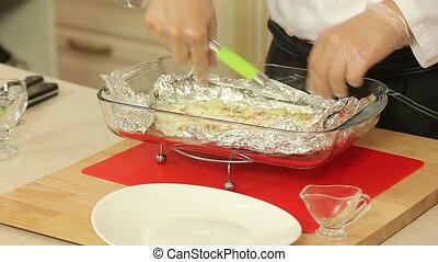 Fish fillet baked in foil - Chef is serving fish fillet...