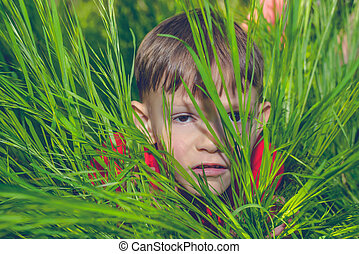 Serious little boy peering out from lush grass - Serious...