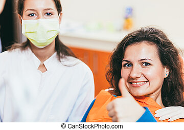 Woman giving thumbs up at dentist office