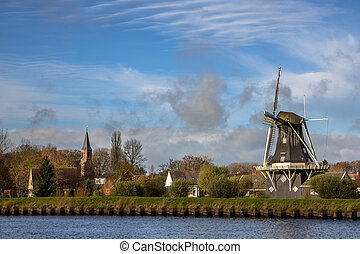 Windmill and church in small village of Woltersum - View of...