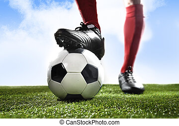 close up legs feet football player in red socks and black shoes playing with ball on grass pitch outdoors