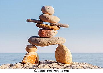 Inukshuk on sea background - Symbolic figurine of inukshuk...