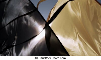 Black and yellow flags waving in wind in sunbeams, summer...