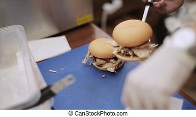 Cook in gloves put cooked hamburger into packet Fast food...