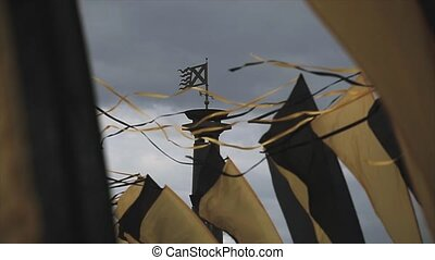 Black and yellow tapes sway on wind in summer day Grey sky...