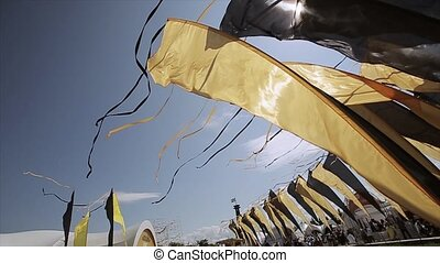 Black and yellow flags with tapes waving from wind in summer...