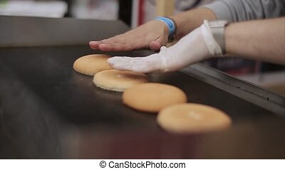 Cook in gloves roast fresh buns for hamburger on stove. Fast food. Open air kitchen. Steam