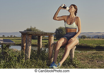 Woman hydrating after run - Attractive young lady in summer...