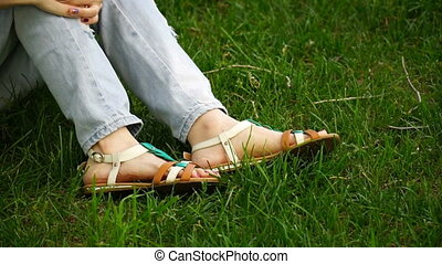 Caucasian young woman sitting on the grass in the park buttons their sandals. Footage girl relaxing outdoor