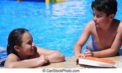 Young boy and girl in pool - Portrait of a young girl and...