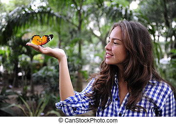 butterfly sitting on the hand of a young woman in the forest...