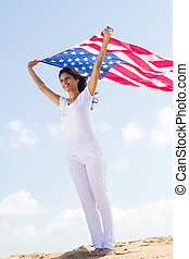 american dreamer - woman with US flag on beach