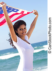 woman on beach holding american flag