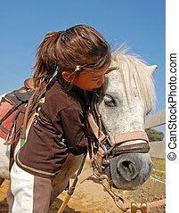 child and pony - little girl kissing her best friend...