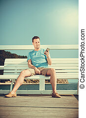 Man tourist on pier using smartphone. Technology. - Handsome...