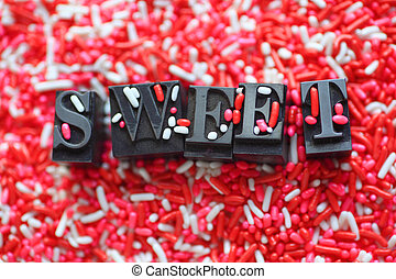 Candy sprinkles with the word sweet