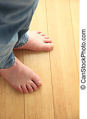 Man stands on floor with bare feet